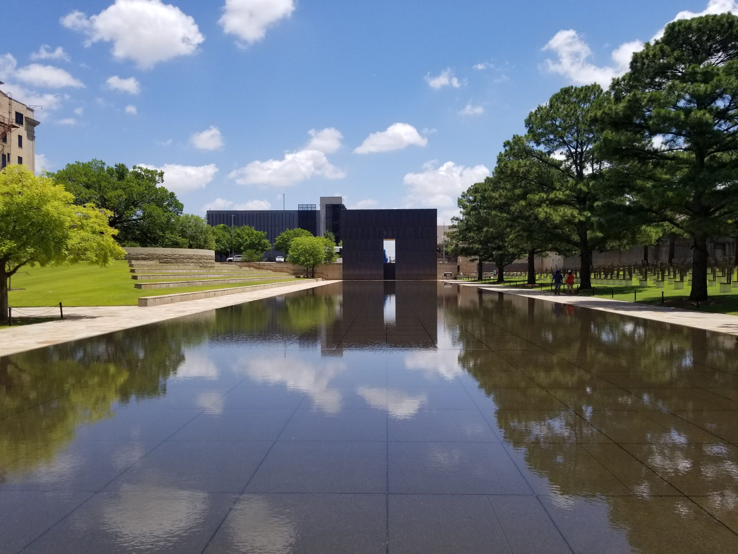 The pool occupies what was once N.W. Fifth Street. Here, a shallow depth of gently flowing water helps soothe wounds, with calming sounds providing a peaceful setting for quiet thoughts. The placid surface creates the reflection of someone changed forever by their visit to the Memorial.